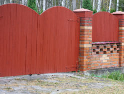 Кирпичный забор с деревянными воротами