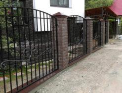 Металлический забор с кирпичными столбами